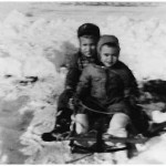 Joe and George Lasica in a typical winter scene, on their sled on their front walk, around 1960.